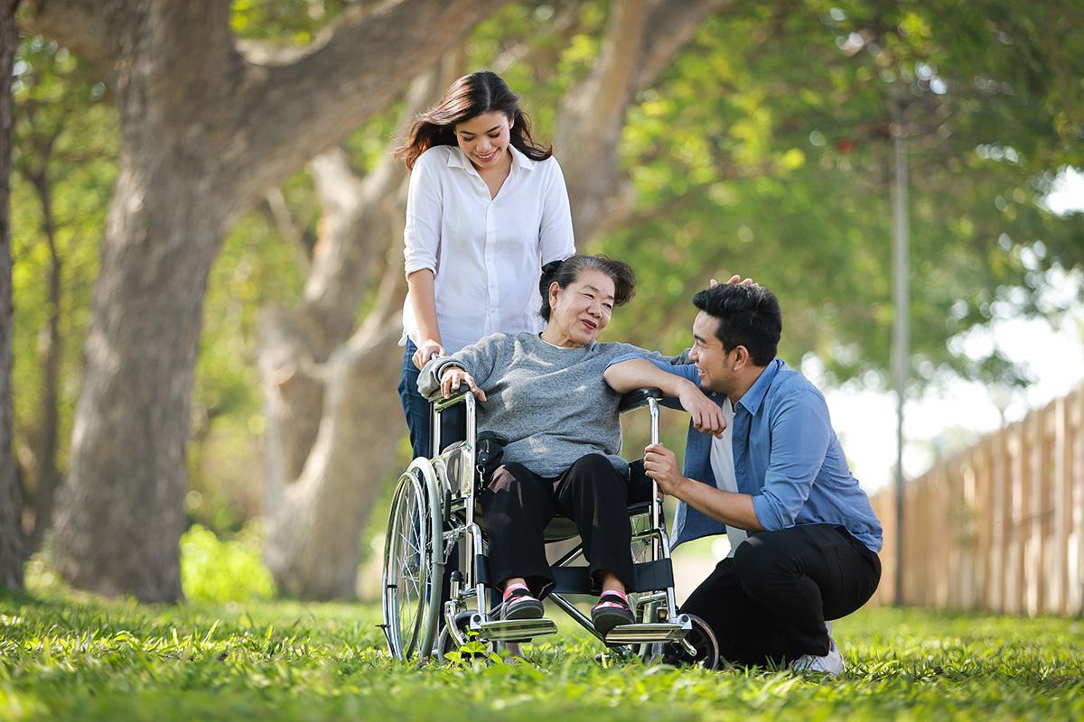 Older woman in a wheelchair with her grandchildren.