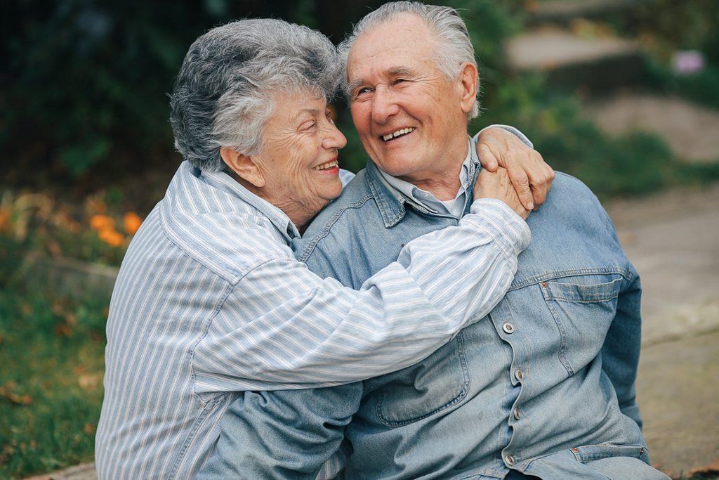 Older couple hugging each other.